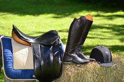Horse riding equipments. Saddle, boots and helmet on hay bale Stock Photos