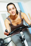 Riding an exercise bike Stock Images