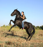 Riding girl. Happy teenager and her black stallion in field Royalty Free Stock Photos