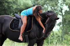 Riding girl. Young teenager stroking her black stallion in a field Royalty Free Stock Photo