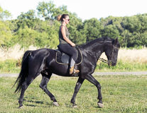 Riding girl on black stallion Royalty Free Stock Images