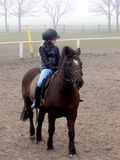 Riding girl in the fog. Young girl riding on horse in the paddock. Horse school in the fog Stock Photo