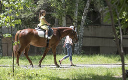 Riding Girl On A Horse In The Park With Guide Stock Photo