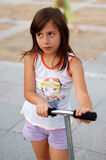Riding her scooter Stock Image