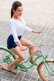 Riding her vintage bike. Royalty Free Stock Photography