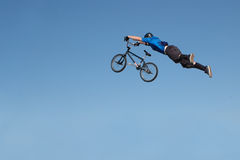 Riding High. Stunt biker flying through air holding onto bicycle.  Solid blue sky provides plenty of space for your text Stock Photos