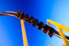 Riding a high speed winding roller coaster at a theme park stock images
