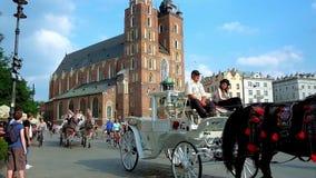 Riding horse-drawn carriages on Plac Mariacki Main Market Square, Krakow, Poland stock video footage
