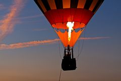 Riding in a Hot Air Balloon at Sunset. Silhouette of a balloonist at sunset as fire illuminates the balloon Royalty Free Stock Photo