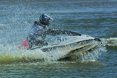 Riding a jetski. Someone riding a jetski, surrounded with water drops Stock Image