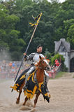 Riding Knight. A knight in armor rides horesback across a tournament field while carrying a standard Stock Image