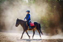 Riding lesson in dust Royalty Free Stock Photos