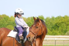 Riding Lessons. A young girl getting her first riding lesson Stock Image
