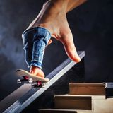 Riding a mini skateboard on a special track. Hand with fingerboard. Closeup royalty free stock image