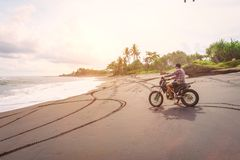 Riding motorbike. A man rides his mountain bike on a beach in Bali. Riding motorbike. A man rides his mountain sport bike on a beach in Bali Stock Image