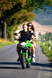 Riding the motorcycle. Young couple riding the motorcycle stock photo