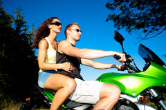 Riding the motorcycle. Young couple riding the motorcycle stock photos