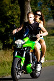 Riding the motorcycle. Young couple riding the motorcycle royalty free stock images