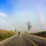 Riding a motorcycle on a foggy street. On a holiday when you ride a motorcycle on a foggy road. Through the corn farm Beautiful scenery makes you relax Royalty Free Stock Photos