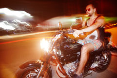 Riding motorcycle on night streets. Without helmet . Long exposure. High speed driving stock photo