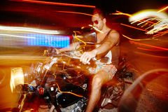 Riding motorcycle on night streets. Without helmet . Long exposure. High speed driving. Side view royalty free stock photo