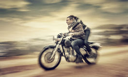 Riding on motorcycle. Two happy people riding on motorcycle, slow motion effect, grunge style photo, romantic relationship, speed and adventure concept stock images