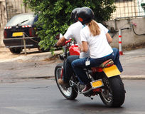 Riding the motrobike. Couple riding a new red motorbike stock image