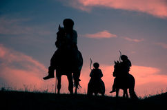 Riding nomadic horsemen on sunset Royalty Free Stock Photo