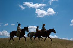 Riding nomadic horsemen on sunset Royalty Free Stock Photography