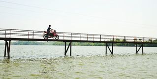 Riding over waters. Motorcycle riding over bridge Stock Photos