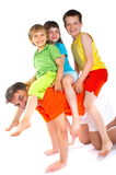 Riding piggyback. Three children ride on their father/uncle's back gleefully Stock Image