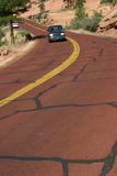 Riding on the Red Road. A driver travels on a red road in Zion National Park in Utah. THIS IS THE 30,000TH IMAGE ONLINE ON DREAMSTIME.COM stock image