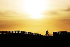 Riding rides bicycle on the bridge Royalty Free Stock Photos