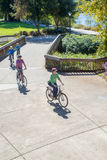Riding By The River. A young family seen from above ride single file along a bike path with a river in the background Royalty Free Stock Images