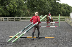 Riding school pupil and instructor with poles for a jump Royalty Free Stock Images