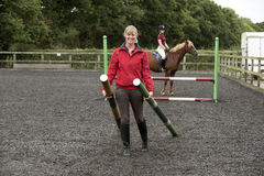 Riding school pupil and instructor with poles for a jump Royalty Free Stock Photo