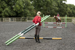 Riding school pupil and instructor with poles for a jump Stock Images