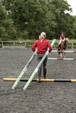 Riding school pupil and instructor with poles for a jump Stock Photo