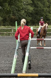 Riding school pupil and instructor with poles for a jump Stock Photography