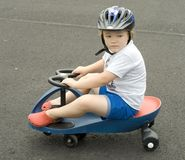 Riding Scooter. Young boy riding blue plasma car on asphalt stock photos