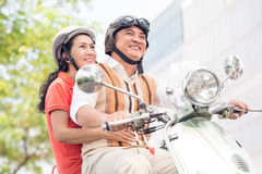 Riding a scooter. Angle view of modern cheerful seniors riding a scooter Stock Image