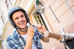 Riding on scooter. Handsome young man is wearing helmet while sitting on scooter Stock Photos