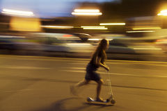 Riding scooter at night Royalty Free Stock Images