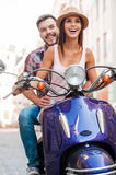 Riding scooter is such a fun!. Beautiful young couple riding scooter along a street and smiling Royalty Free Stock Photography