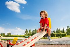 Riding seesaw. Happy little three years old child riding seesaw with big smile and happy face Royalty Free Stock Image
