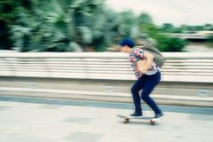 Riding on skateboard. College student riding on skateboard, blurred motion Stock Photography