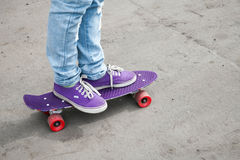 Riding skateboarder feet in blue jeans and gumshoes Royalty Free Stock Image