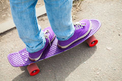 Riding skateboarder feet in a blue jeans Royalty Free Stock Photo