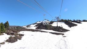 Riding the ski lift in summer snow Royalty Free Stock Image