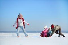 Riding on sledge. Happy kids enjoying riding on sledge Royalty Free Stock Photo
